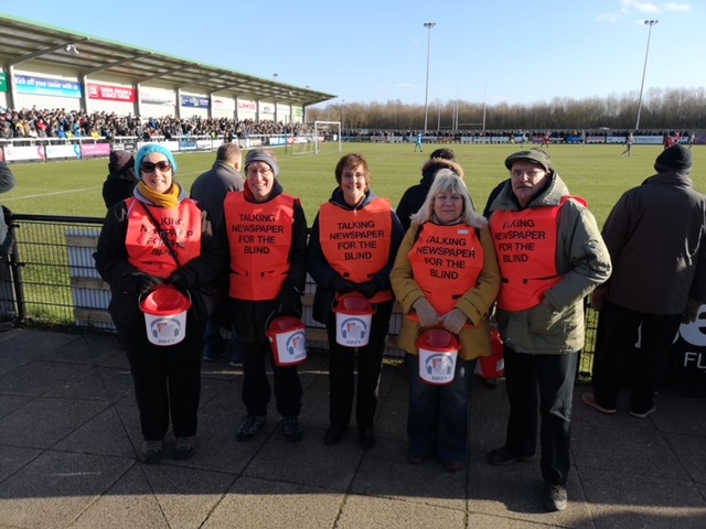 Members of the Darlington Talking Newspaper team stood pitch side at Darlington FC's ground with hi viz jackets and fundraiising buckets.